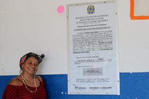 dada lider comunitaria em frente a placa da escola quilombola