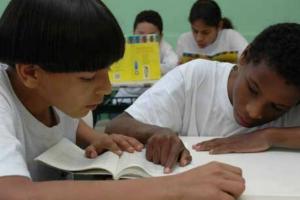 dois alunos se ajudam nas tarefas na sala de aula