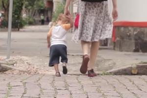 crianca de 1 ano e meio andando de mão dadas com a mãe na rua